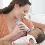 Hispanic mother bottle feeding baby