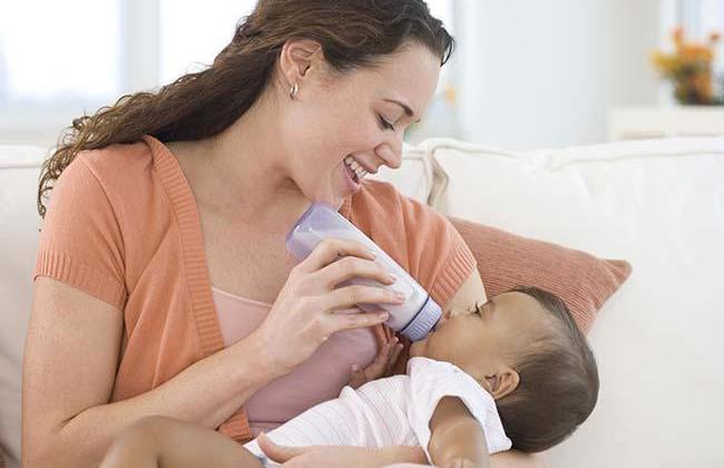 Hispanic mother bottle feeding baby